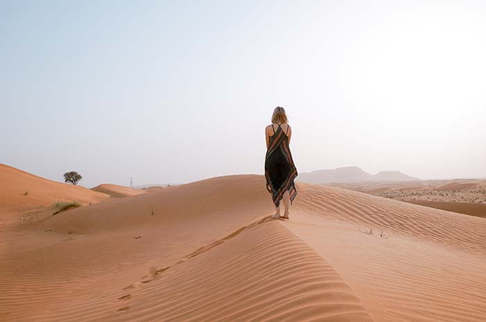 Mädchen auf einer Düne in der Wüste
