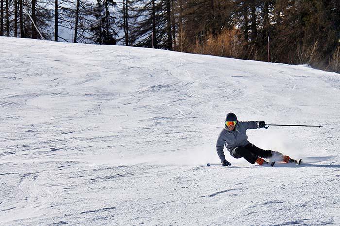 Skifahrer auf einer Abfahrt im Wald