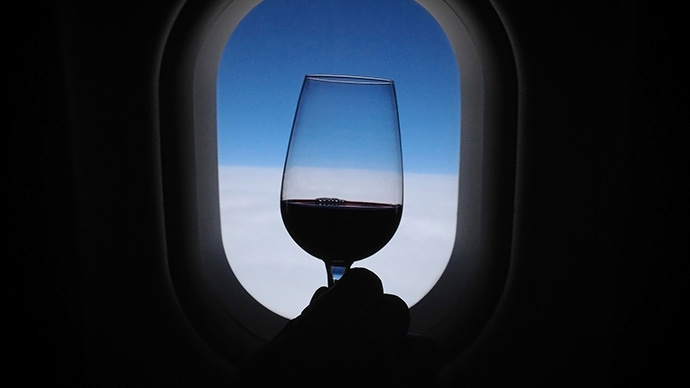 Weinglas vor Flugzeugfenster - Benimmregeln im Flugzeug