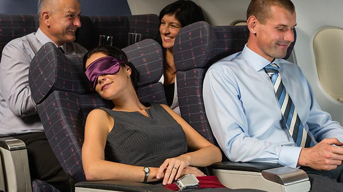 Frau schläft im Flugzeug mit Augenbinde