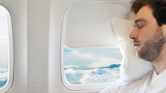 Junger Mann beim Schlafen im Flugzeug